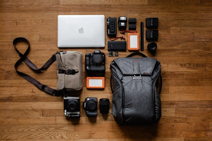 Laptop, camera with accessories on a wooden table