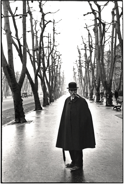 a black and white henri cartier-bresson image of a man within two rows of trees