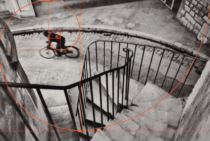 a black and white henri cartier bresson of a cyclist shot from above with fibonacci spiral overlay