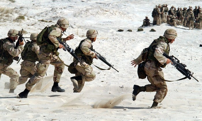 a photo of military troops running in the sand