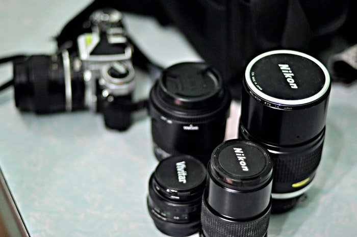 Four canon lenses beside a camera