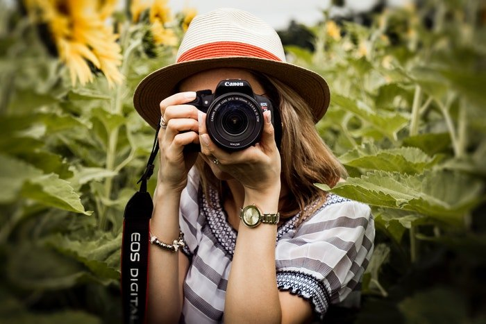 A female photographer taking photos' in a field with a Canon DSLR