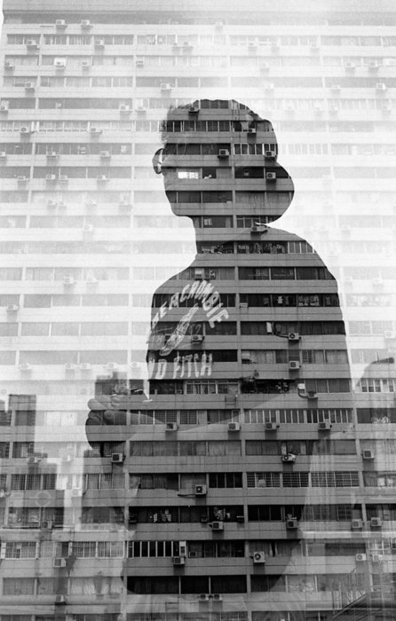 double exposed portrait of a man and a multifloored building