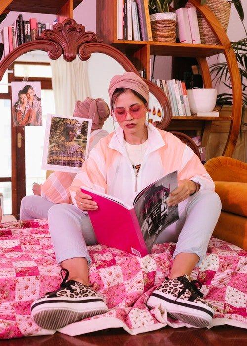 a imagem de uma mulher sentada no chão lendo uma revista com óculos escuros