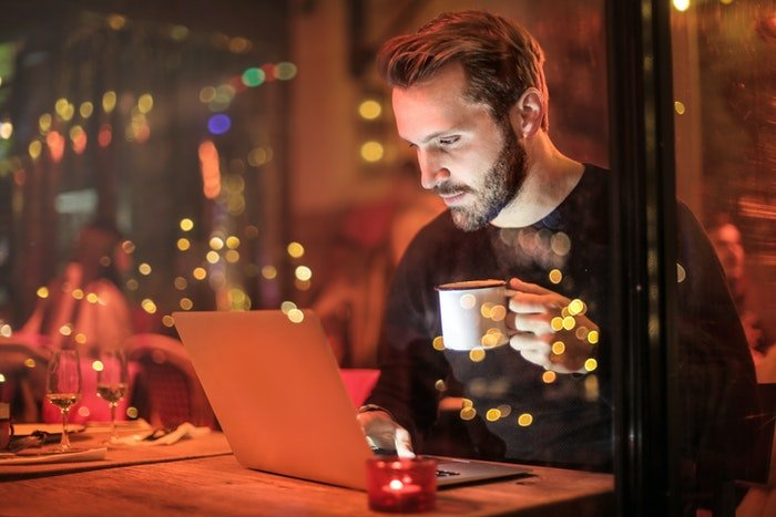 Uma imagem de um homem sentado em seu computador segurando uma xícara de café disparada por uma janela à noite