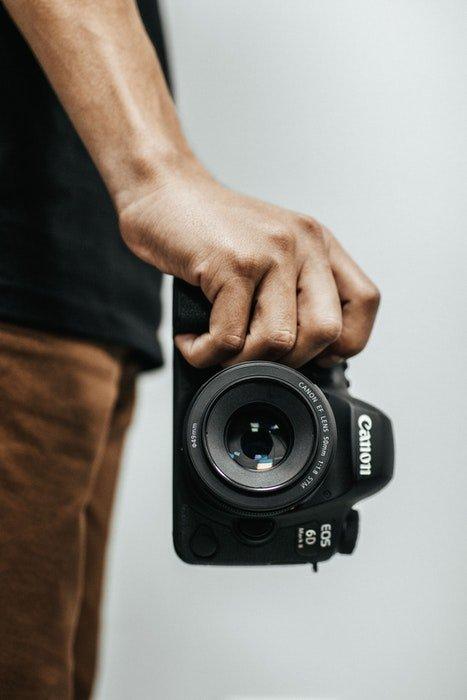 uma imagem em close-up da mão de um homem segurando uma Canon EOS 6D