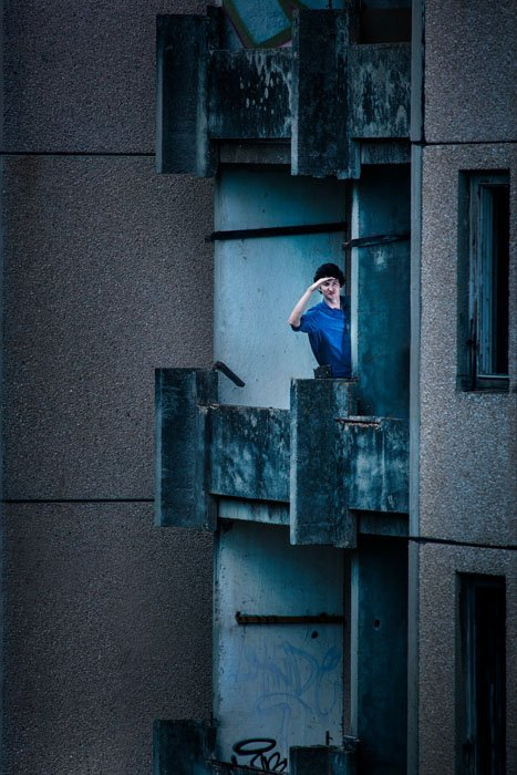 A person standing on an apartment balcony