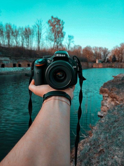 拿着一个照相机的人反对美丽的河