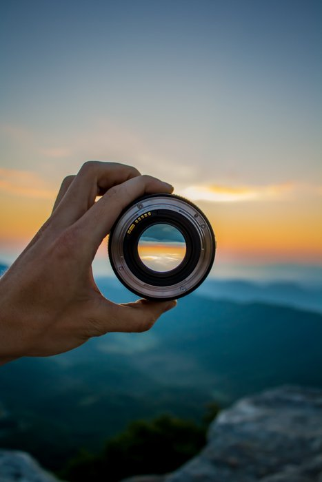 一个人拿着相机镜头对着美丽的日落