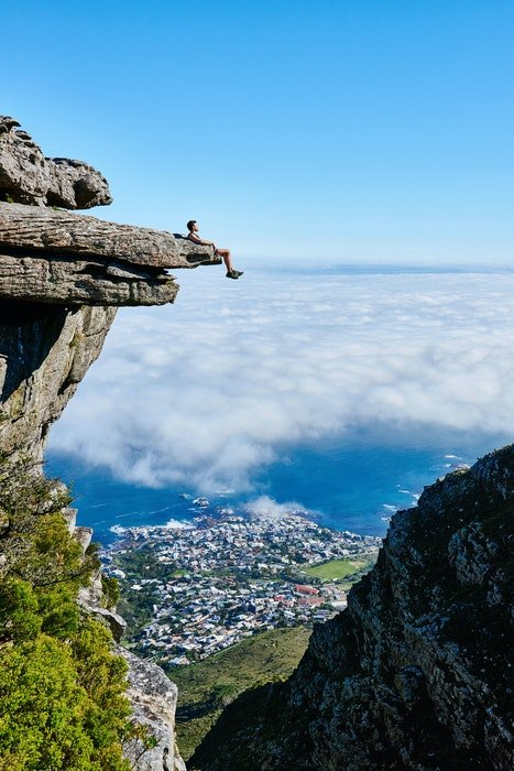 an image of a climber resting on a cliff face with a city in the distant background