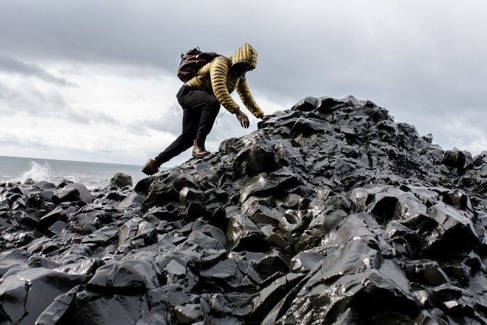 A climber climbing rocky terrain next to a beach with good lead room