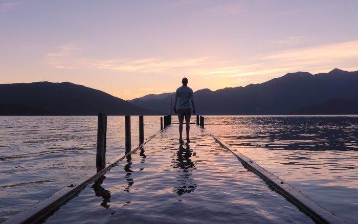 an image of a man walking towards a lake at sunset