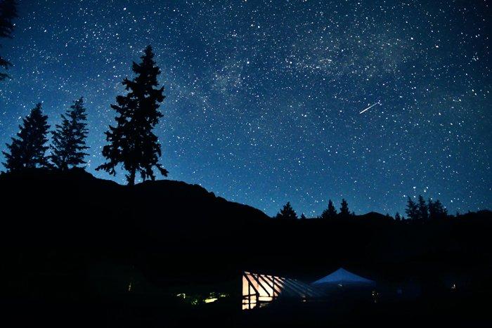 meteor shower captured over dark landscape