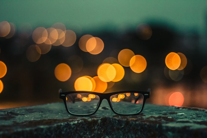 close-up of a pair of glasses with yellow bokeh photography effect in the background