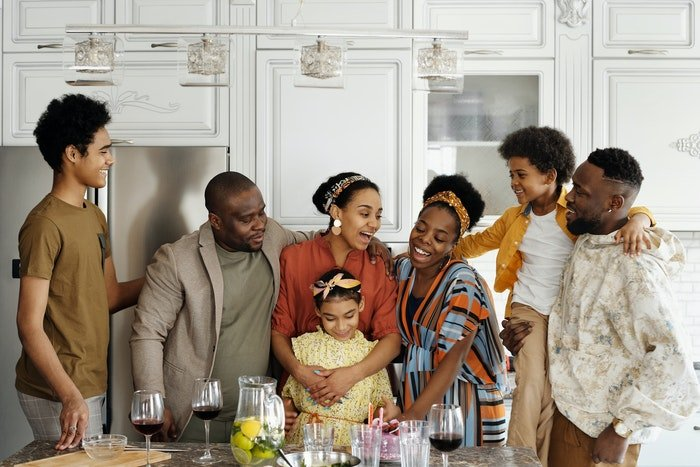 A large family posing in a kitchen