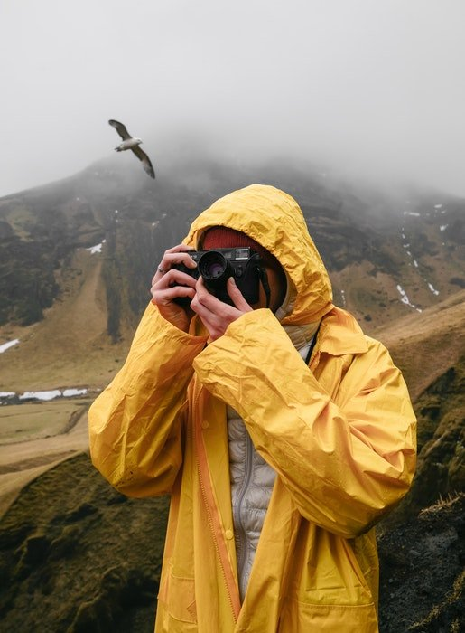 a photographer in yello shooting on a rainy day in the mountains with a bird behind him