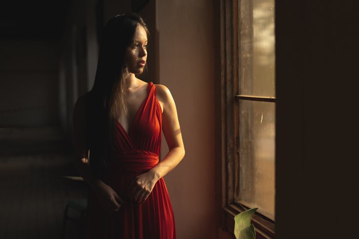 photo of a woman in a red dress standing next to the window and looking outside