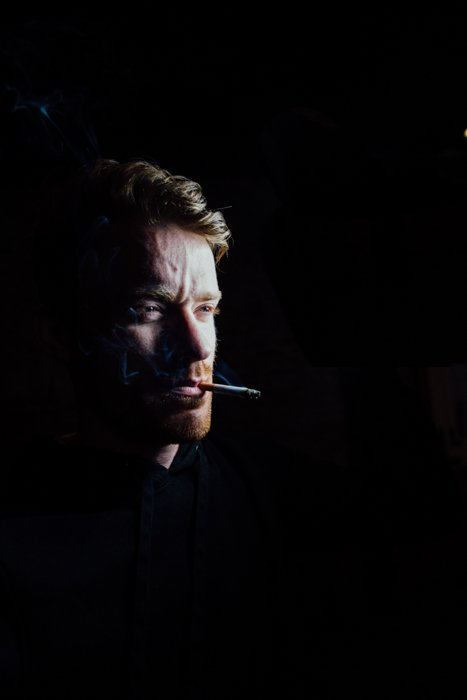 Dark studio portrait of a man with black background