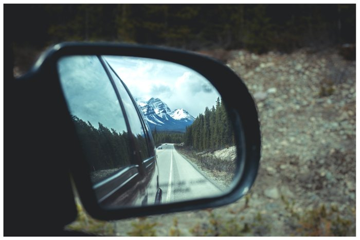 photo of a mountain reflected in a car mirror