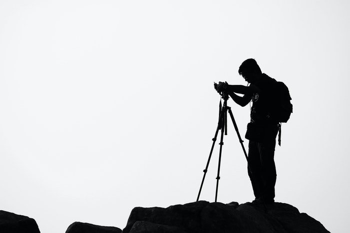 Silhouette of a photographer setting up his camera on a tripod