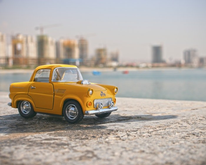 A toy yellow taxi car on a wall