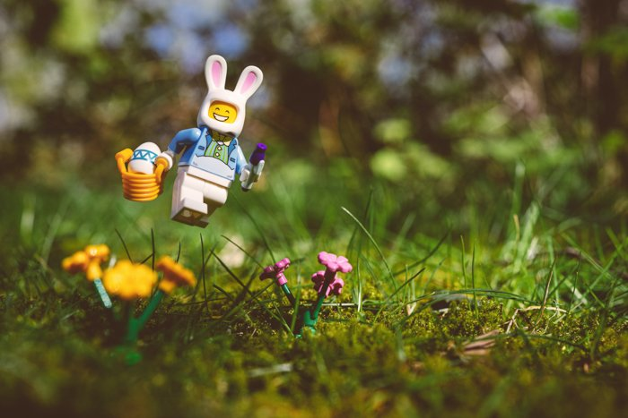 Cute toy photography of a lego figure dressed as an easter bunny skipping through the grass