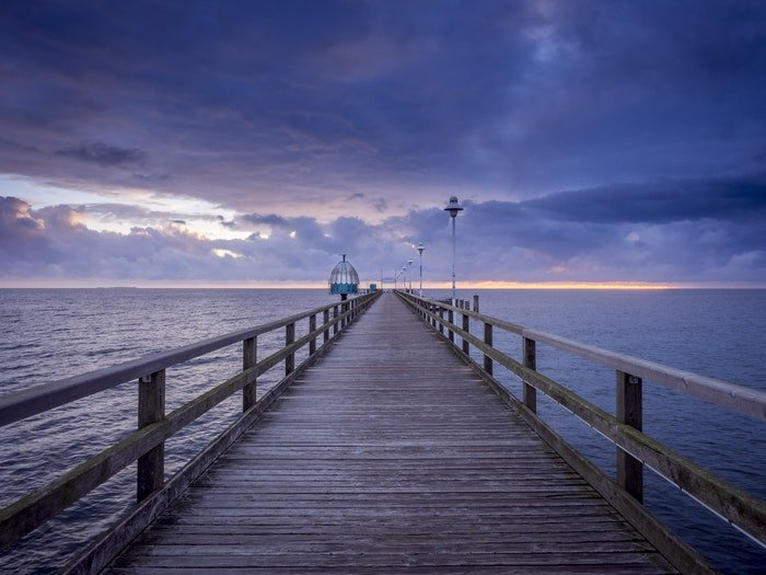 A wooden pier at sunset demonstrating vanishing points in photography