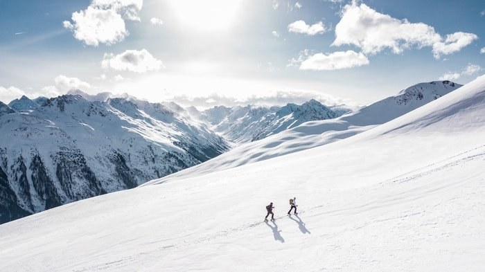 Two hikers walking on a mountain with balanced visual weight of mountains in the background