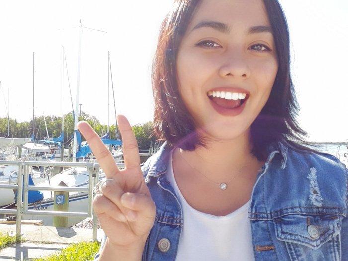 A girl giving V finger sign outdoors