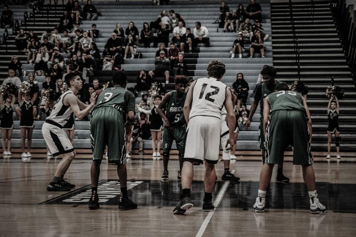 7 jogadores em um jogo de basquete, esperando que um deles lance a bola.