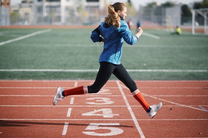 Uma mulher correndo em uma pista de corrida, enquanto ouve música.
