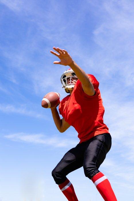 Vista frontal de baixo ângulo de um jogador de futebol americano de raça mista, usando uniforme do time, treinando em uma quadra de esportes, preparando-se para lançar uma bola de futebol, com céu azul ao fundo