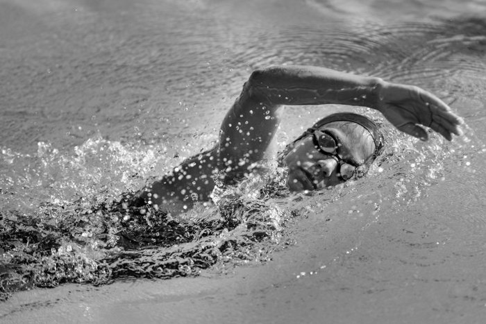 Imagem preto e branco de uma mulher nadando em uma piscina.