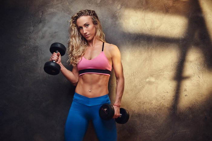 Jovem mulher está fazendo exercícios com halteres em um quarto escuro.