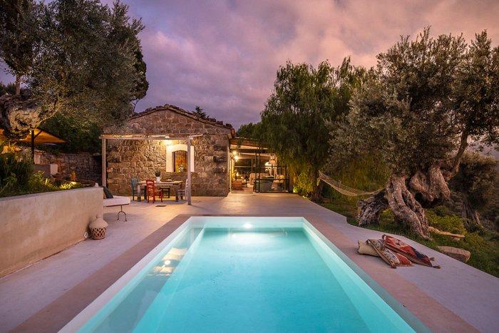 Uma foto de um imóvel no crepúsculo de uma casa de pedra com uma piscina em primeiro plano