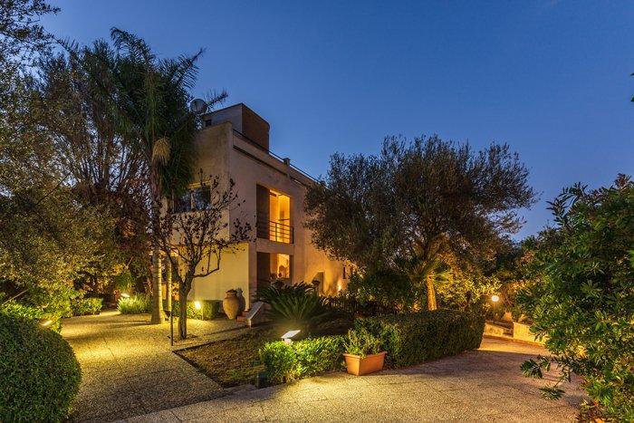 uma foto de crepúsculo de uma casa moderna e jardim