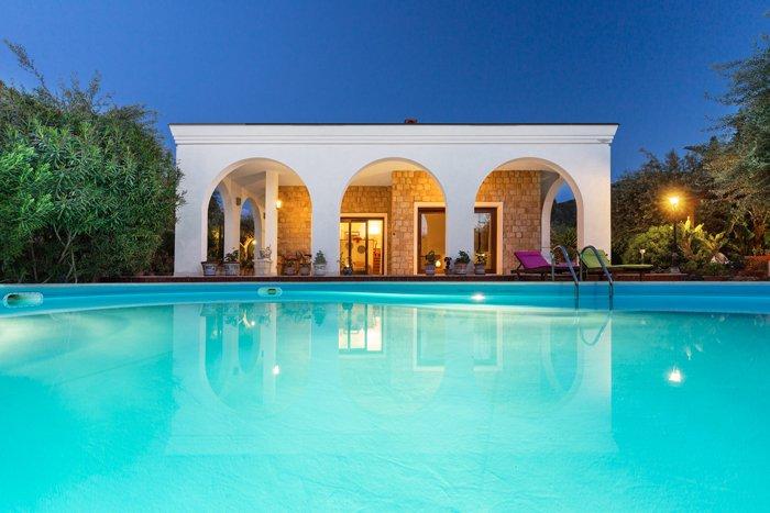 Uma fotografia de um imóvel no crepúsculo de uma pequena casa com uma piscina em primeiro plano cercada por arbustos