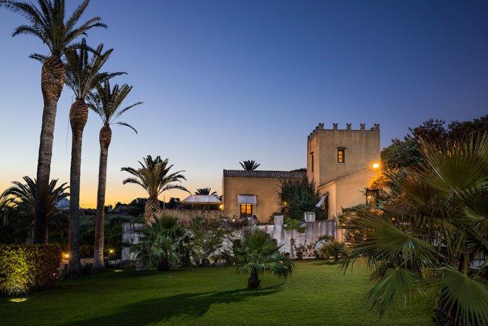 uma foto de um castelo no crepúsculo, como uma casa em um lugar tropical
