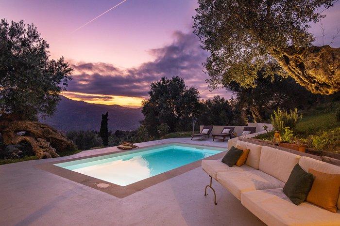 Uma foto do crepúsculo do exterior de uma casa com piscina e sofá contra um céu rosa