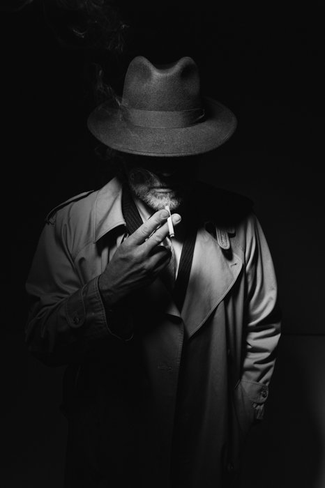 Man with fedora hat and trench coat smoking a cigarette in the dark, 1950s noir film character