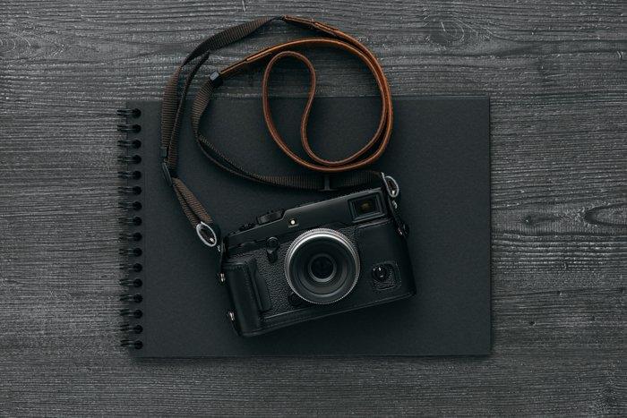 Empty black photo album and professional digital camera with a leather camera strap on a dark desktop