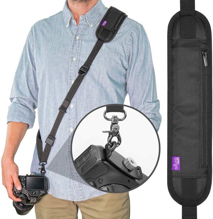 A man wearing a black camera shoulder strap