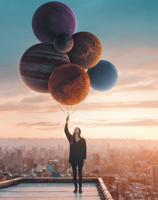 Fine art photo of a girl holding planets as balloons