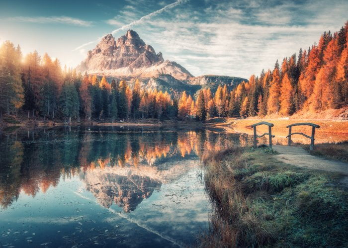 Lake with reflection in mountains at sunrise in autumn in Dolomites, Italy. Landscape with Antorno lake, small wooden bridge, trees with orange leaves, high rocks, blue sky in fall. Colorful forest