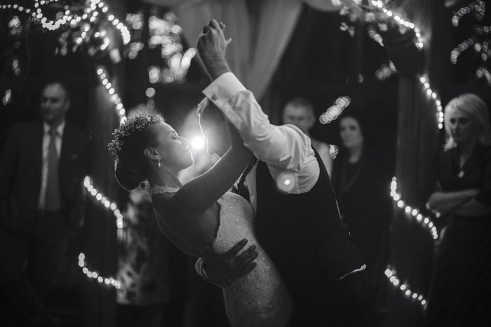 Black and white image of the wedding dance of beautiful young newlywed couple