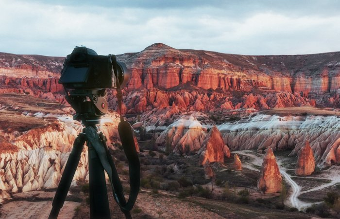 Beautiful sunset over the canyon in cappadocia turkey with a DSLR camera on a tripod in the foreground