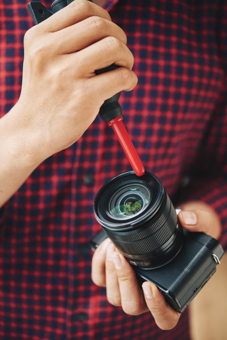 A man cleaning his camera lens with a black and red blower and lens cleaning solution.