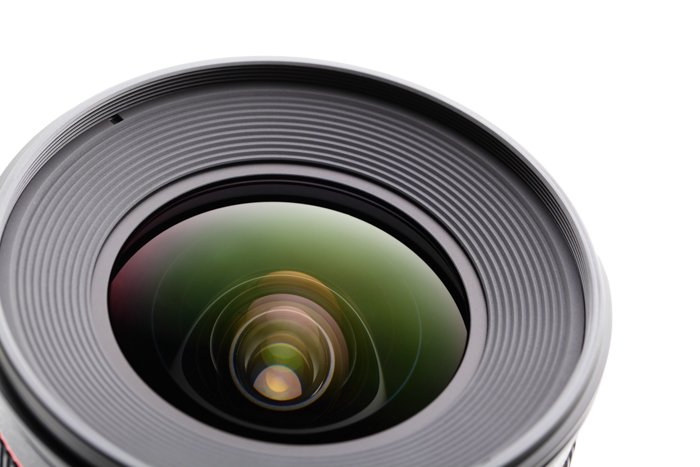 close up of a camera lens against a white background