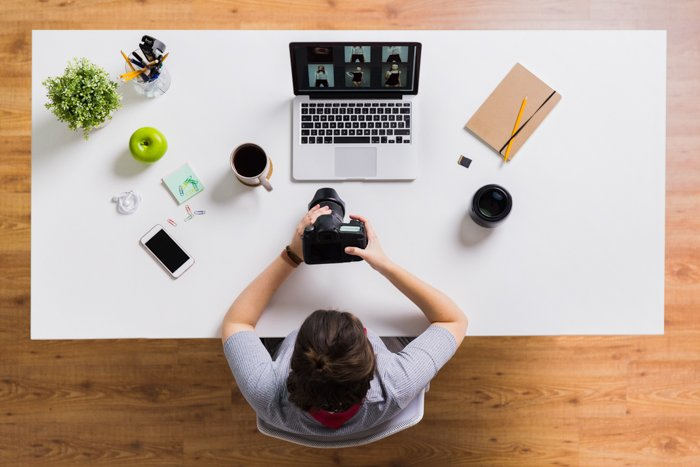 A woman from above, with a camera in her hands, and with a laptop, a mobile, an apple and coffee on the office table