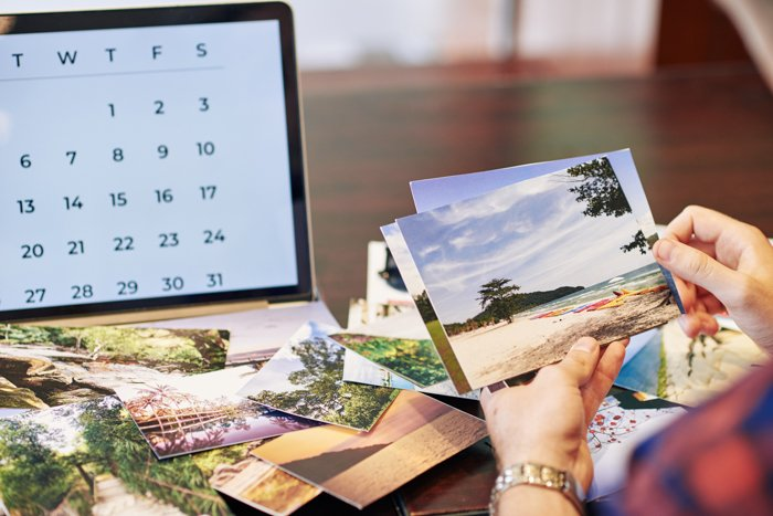 Hands of traveler checking photos he printed after summer vacation